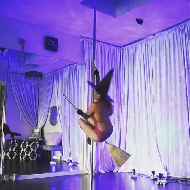 Woman in Witch's Hat Pole Dances Holding a Broomstick | Jukin Media Inc